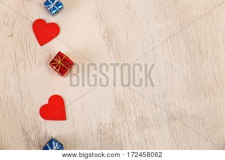 Red hearts and gift boxes on rustic wood background. Valentines day or 8 march design. Romantic love. Wooden grunge board.