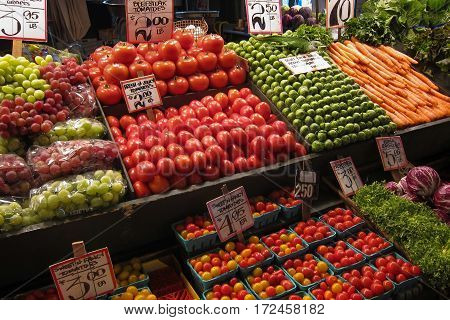 Colorful display of vegetables and fruits on sale at farmer's market, arranged in boxes