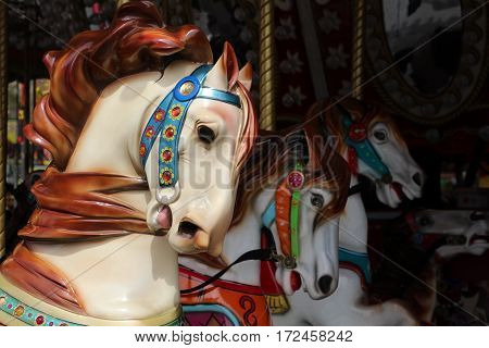 Close up of merry-go-round bejeweled horses galloping, manes flying, one prominent.