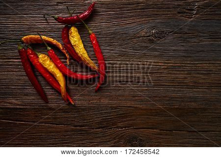 dried hot chili peppers on aged wood background