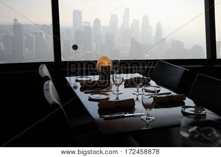 Misty view of Seattle skyscrapers from empty set table in restaurant in Space Needle