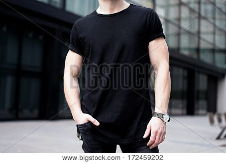 Young muscular man wearing black tshirt and jeans posing in center of modern city. Blurred background. Hotizontal mockup