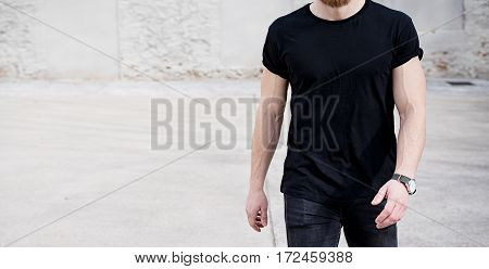 Young muscular man wearing black tshirt and jeans walking on the urban district. Blurred background. Hotizontal wide mockup