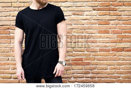 Closeup view of bearded muscular man wearing black tshirt and jeans posing outside. Empty brown grunge brick wall on the background. Hotizontal mockup