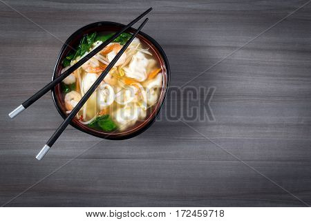 dumpling and prawn wonton asian soup bowl on grey table