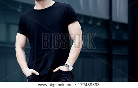 Closeup of young caucasian muscular man wearing black tshirt and jeans posing in center of modern city. Blurred background. Hotizontal mockup