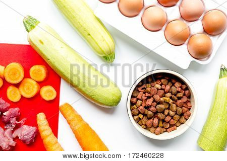 healthy dogfood with eggs, fresh vegetables and raw meat on white kitchen table background top view
