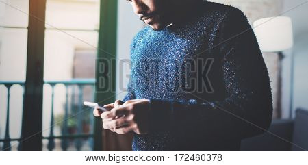 Pensive young African freelancer typing screen of mobile phone while working in new project at home.Black man looking for information on Internet.Blurred, crop, flares