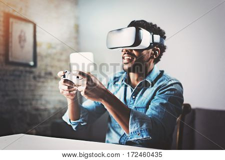 Concept of technology, gaming, entertainment and people.African man enjoying virtual reality glasses while relaxing in living room.Happy young guy with VR headset playing video game at home.Blurred