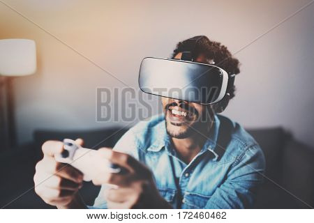Concept of technology, gaming, entertainment and people.African man playing virtual reality glasses video game while relaxing in living room at home.Selective focus on VR headset.Blurred background