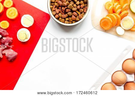 Dry dogfood, eggs, raw meat, fresh carrot and courgette on kitchen table background top view mock-up