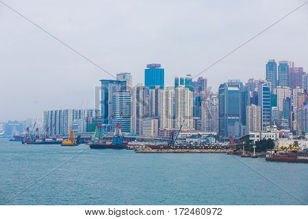 Beautiful super wide-angle summer aerial view View of Hong Kong island skyline, Victoria Bay harbor, with skyscrapers, blue sky and scenery beyond the city, seen from Kowloon island observation Deck
