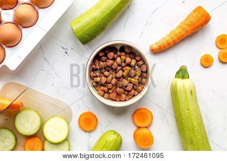 Fresh vegetables and dry petfood on white kitchen table background top view