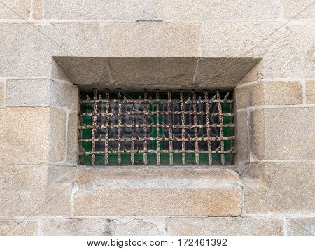 metal grille on the window in the stone wall