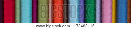Close up of multiple brightly colored spools of thread photographed and eye level.