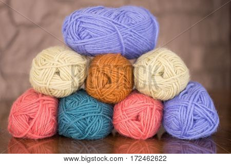 Eight skeins of wool yarn in lavender, gold, pink, turquoise and cream. All on wooden table with a stone wall in background