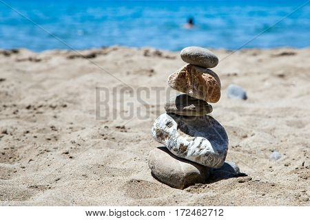 stones stacked tower on a sandy sea beach