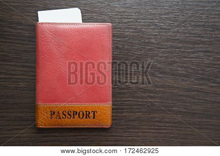passport and airline tickets in orange leather cover on a table