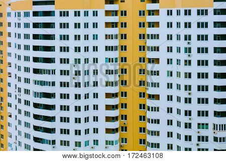 Hundreds of windows on unfinished high building. Skyscraper with yellow patterns