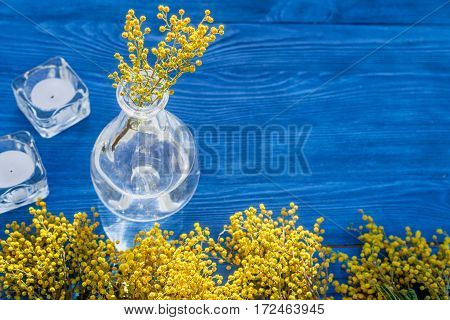 mimosa on wooden background in glass vase close up mock up