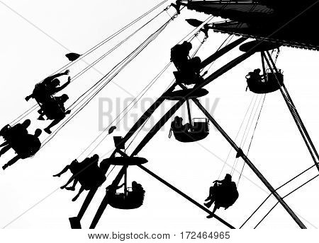 Silhouetted riders on a Flying Swing and a Ferris wheel at a summer fair