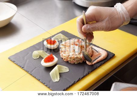 Chef is decorating crab salad with sauce in restaurant kitchen