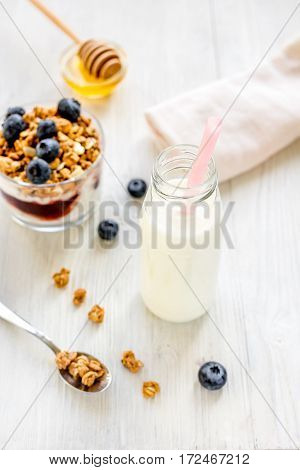 Fitness breakfast with homemade granola from yoghurt, flake and berries, milk and honey on white desk background