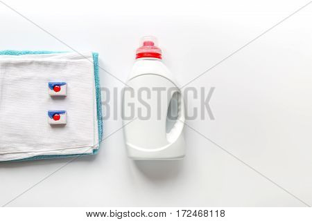 laundry set with bright towels and plastic bottels of detergent on white table background top view mock-up