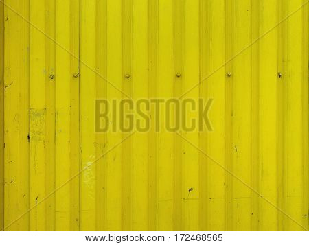 Metal bright yellow dirty old background texture with screws in the upper part.