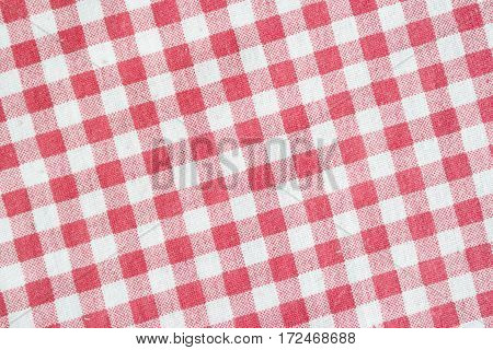 Red and white checkered fabric texture. Red picnic tablecloth background.