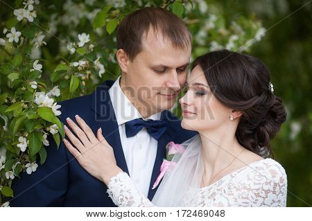 Young newlywed groom and bride in blooming garden wedding or marriage concept