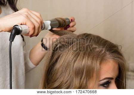 Barber stylist makes a girl hairstyle at the beauty salon.