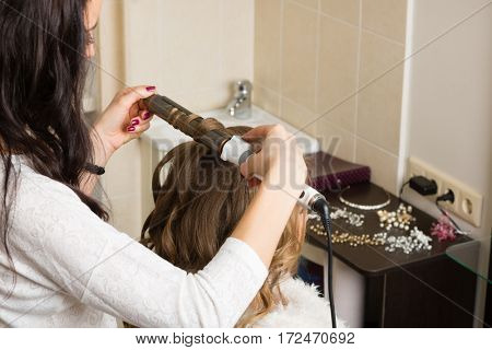 Hairdresser curling works with the client in the beauty salon.