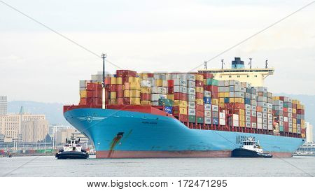 Oakland CA - January 31 2017: Multiple tugboats assist cargo ship GEORG MAERSK to maneuver into the Port of Oakland.
