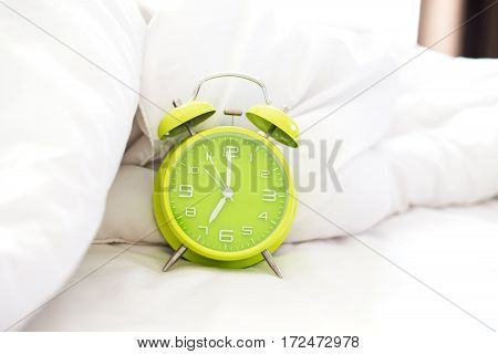 Alarm clock on bed in morning with sun light Greenery soft and select focus