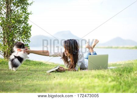 Girl and puppy dog enjoy listening music on the grass field of the park in the morning