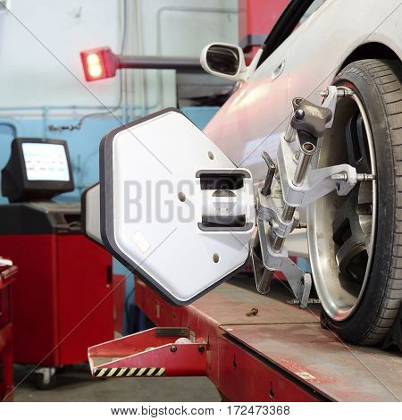 Wheel alignment equipment on a car wheel in a repair station in Moscow, Russia