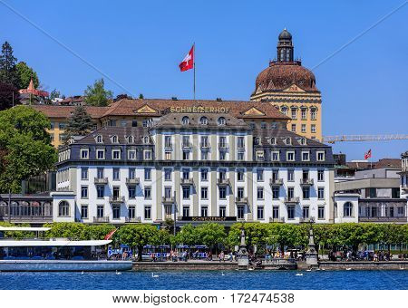 Lucerne, Switzerland - 8 May, 2016: people on the embankment of Lake Lucerne, building of the Hotel Schweizerhof decorated with flag of Switzerland. Lucerne is a city in central Switzerland, it is the capital of the Swiss canton of Lucerne.