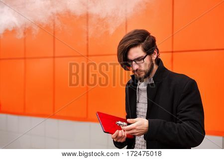 Young hipster man with a beard and glasses smokes an electronic cigarette. He holds a tablet pc. Youth fashion. Delicious pairs. Without nicotine liquid.