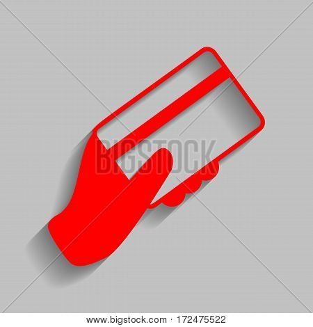 Hand holding a credit card. Vector. Red icon with soft shadow on gray background.