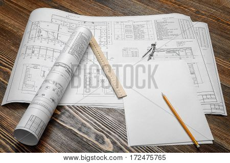 A set of open and rolled up blueprints on wooden table background with a pencil, a ruler and compasses lying beside. Engineering and design. Construction projects. Planning.