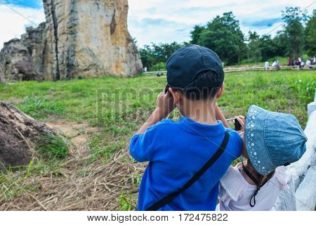 Back view of asian children taking photos by camera at national park . Family relaxing outdoors with bright sunlight at the day time on summer day travel on vacation. Child in nature.