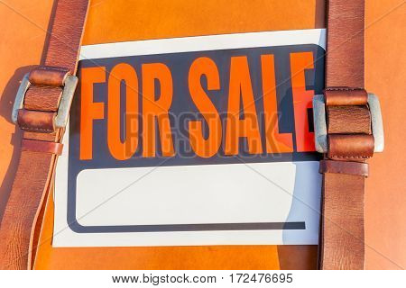 Close-up shot of for sale sign stick on brown leather traveling bag vintage style and two fasten belts.
