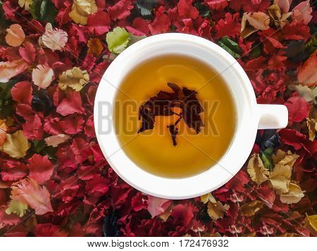 Top view of a cup of hot tea on colorful artificial flowers background.