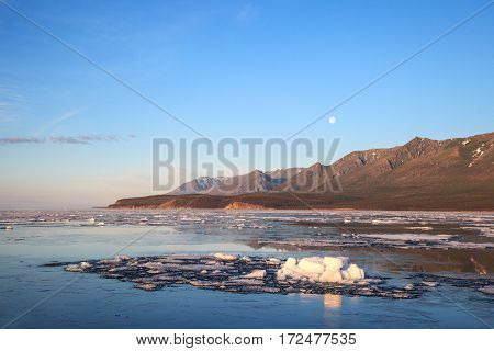 Ice floes drifting on water surface mountains and blue sky with moon on background