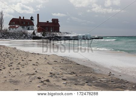 A frozen Point Betsie Lighthouse on the beach in winter