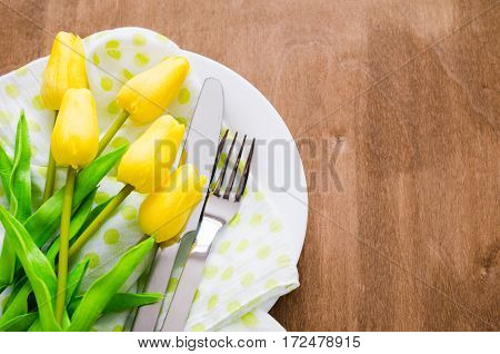 Festive Table Setting in White Green and Yellow With Tulip. Concept Spring Easter or Mother's Day. Selective Focus.