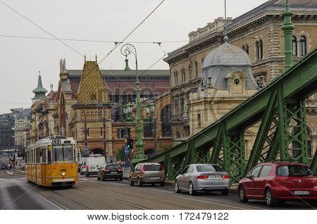 Budapest, Hungary - November 18, 2010: The yellow classical tram on the Liberty bridge across river Danube with Great Market Hall at background Budapest Hungary