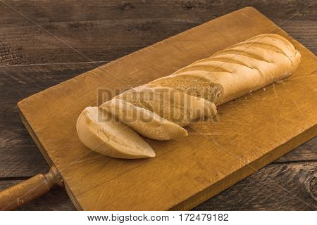 A photo of a loaf of white bread cut into slices on a rustic board with a place for text
