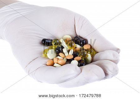 Pharmaceutical pills on a hand in latex glove on a white background